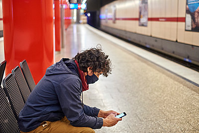 Man wearing facial mask on train platform - p1146m2187830 by Stephanie Uhlenbrock