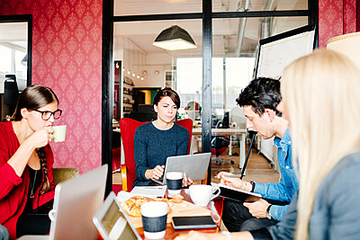 Business people discussing at table in office - p1264m1121926f by Astrakan