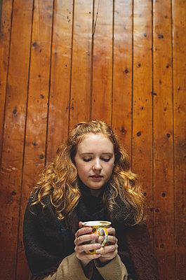 Woman holding a coffee mug in cafe - p1315m2062640 by Wavebreak