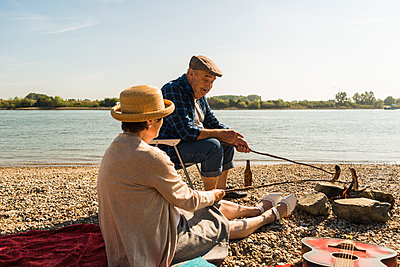 Germany, Ludwigshafen, senior couple barbecueing sausages on the beach - p300m1068771f by Uwe Umstätter