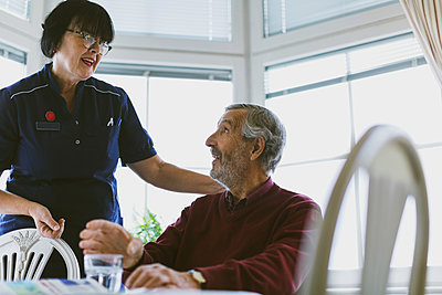Senior man talking to female caretaker at home - p426m1468228 by Maskot