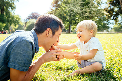 Father and son playing in grass in park - p555m1410989 by Inti St Clair photography