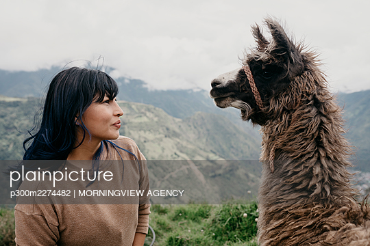 Woman with bangs looking at Alpaca - p300m2274482 by MORNINGVIEW AGENCY