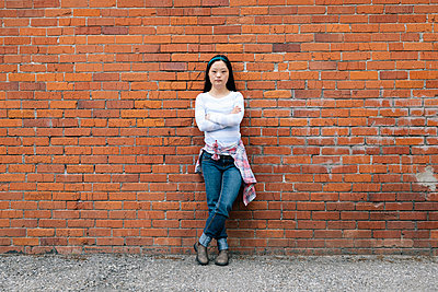 Portrait confident young woman with down syndrome leaning against brick wall - p1192m2110018 by Hero Images