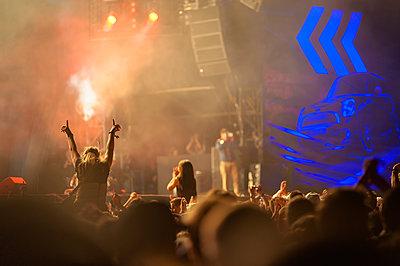 Junge Frau mit emporgestreckten Armen auf dem Rücken eines Begleiters auf einem Open-Air-Konzert - p1400m1582924 von Bastian Fischer