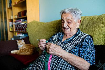 Portrait of crocheting senior woman sitting on couch besides her sleeping cats - p300m2030187 von Ramon Espelt