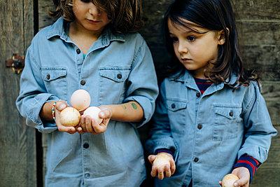 Two kids holding eggs at chicken coop on an organic farm - p300m2144432 von Sofie Delauw