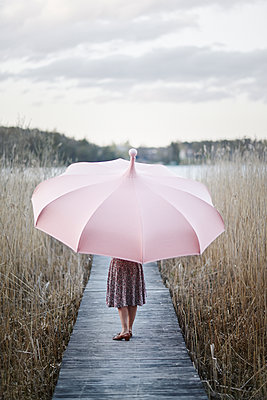 Sweden, Sodermanland, Woman with umbrella standing on wooden pier - p352m1349131 by Fredrik Ottosson