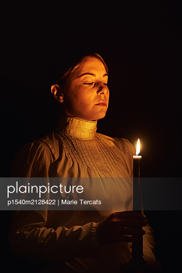 Woman holding a candle  - p1540m2128422 by Marie Tercafs