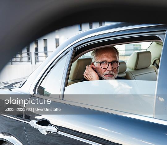 Mature businessman sitting on backseat in car, using earphones - p300m2023763 von Uwe Umstätter