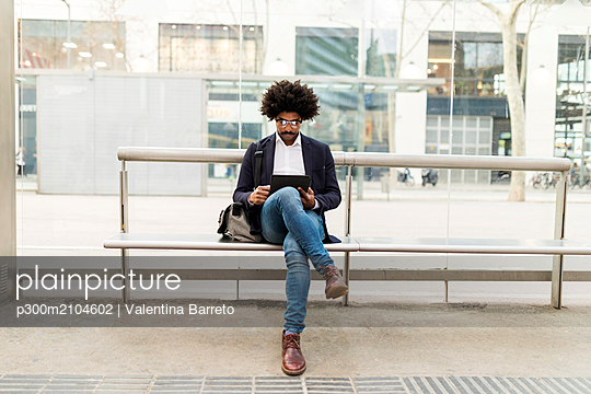 Spain, Barcelona, businessman in the city sitting on bench at a station using tablet - p300m2104602 by Valentina Barreto