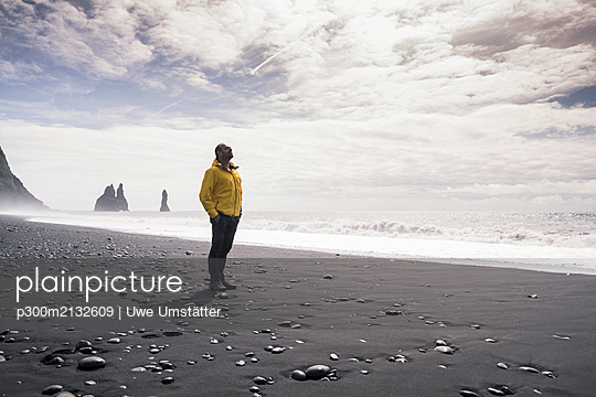 Mature man walking on a lava beach in Iceland - p300m2132609 by Uwe Umstätter