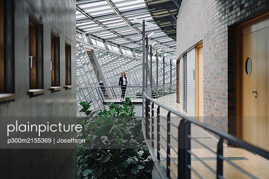 Businesswoman standing on a skywalk in modern office building - p300m2155369 by Joseffson
