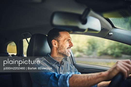Handsome man driving a car - p300m2202460 by Bartek Szewczyk