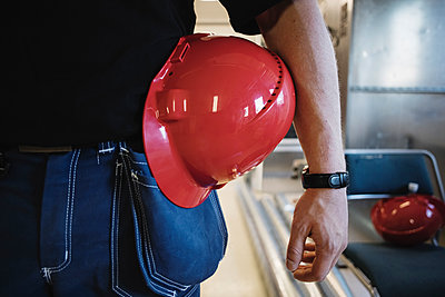 Midsection of auto mechanic teacher with red hardhat while standing at workshop - p426m1130939f by Maskot