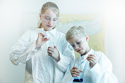Brother and sister wearing safety goggles doing science experiment - p429m803671f by Sigrid Gombert
