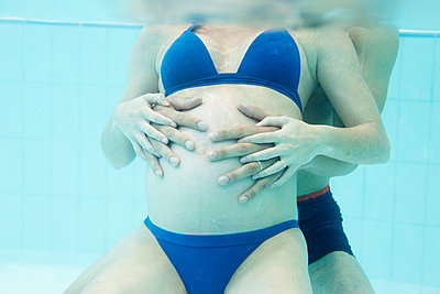 Pregnant woman exercising with help of partner in swimming pool - p623m1221368 by Anne-Sophie Bost