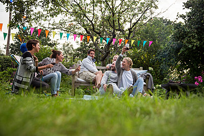 Freunde feiern eine Gartenparty - p788m1165277 von Lisa Krechting