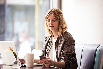 Junge Frau mit Smartphone in einem Cafe - p788m1466103 von Lisa Krechting