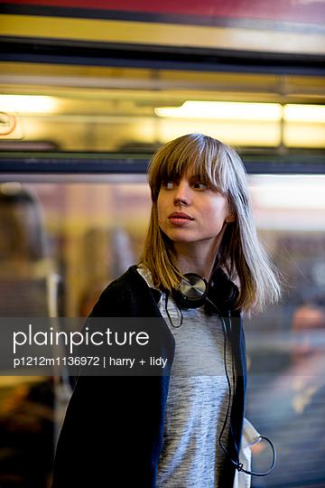Junge Frau vor wegfahrende S-Bahn  - p1212m1136972 von harry + lidy