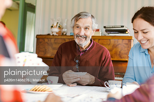 Smiling senior man playing cards with family at home - p426m1468276 by Maskot