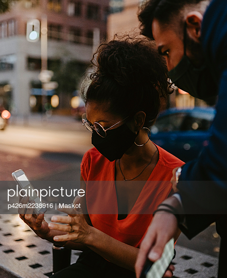 Female entrepreneur using smart phone with male colleague in city during pandemic - p426m2238916 by Maskot