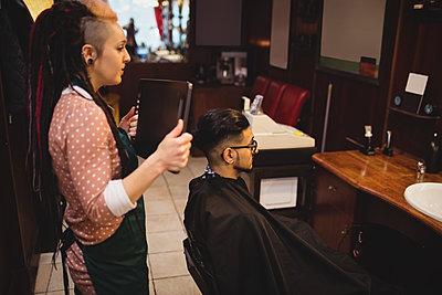 Female barber showing man his haircut in mirror - p1315m1199614 by Wavebreak