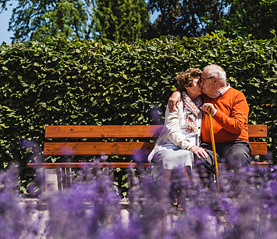 Senior couple sitting on bench in a park, kissing - p300m2030425 by Uwe Umstätter