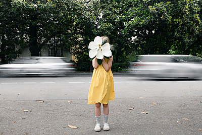 Girl wearing yellow dress hiding her face  behind oversized white magnolia blossom - p300m2103290 by Ekaterina Yakunina