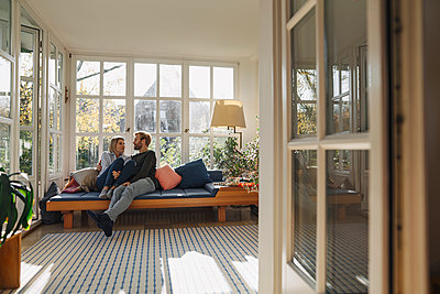 Affectionate couple relaxing in sunroom at home - p300m2205502 by Kniel Synnatzschke