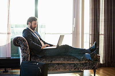 Businessman using laptop on chaise longue in hotel room - p426m920194f by Maskot