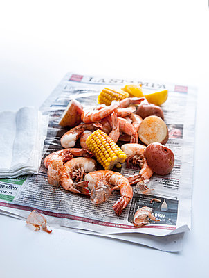 Seafood boil on newspaper - p555m1303416 by Manny Rodriguez