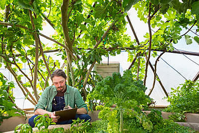 Caucasian gardener writing on clipboard in greenhouse - p555m1410489 by Marc Romanelli