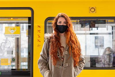 Deutschland, Berlin, Junge Frau mit Nasen-Mund-Maske, Portrait - p975m2223633 von Hayden Verry
