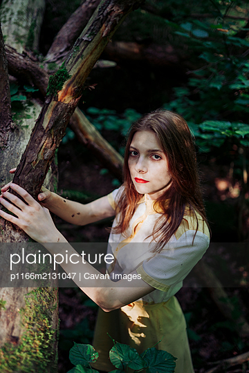 A woman holds on to a branch of a tree in the forest - p1166m2131047 by Cavan Images