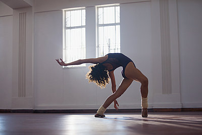 Graceful, flexibility young female dancer practicing in dance studio - p1023m2001441 by Sam Edwards