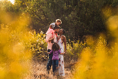 Romantic parents kissing while standing with daughters on field against trees in park - p1166m2067278 by Cavan Images