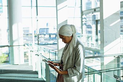 Businesswoman in hijab working on digital tablet near railing in a modern office - p1315m2130115 by Wavebreak