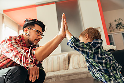 Father and son high fiving - p300m1204422 by Zeljko Dangubic