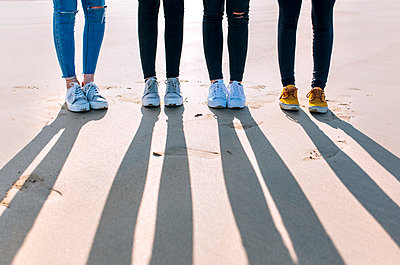 Legs of four friends standing side by side on the beach - p300m1228822 by Marco Govel