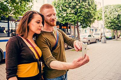 Caucasian couple using cell phone on city sidewalk - p555m1411605 by Aleksander Rubtsov