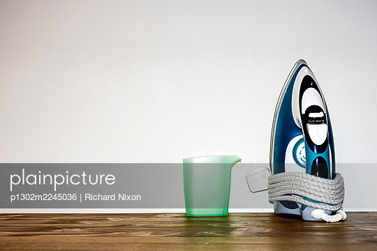 Steam iron and jug on wooden table - p1302m2245036 by Richard Nixon