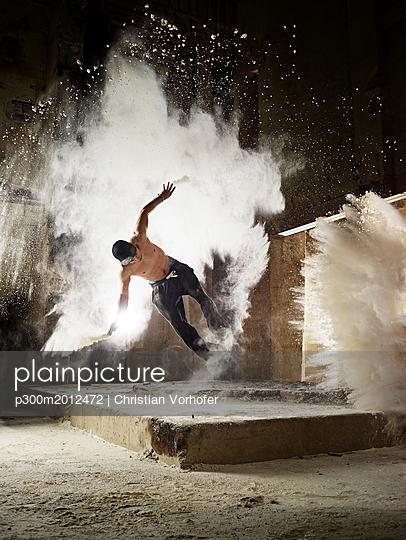 Man jumping in flour dust cloud during freerunning exercise - p300m2012472 von Christian Vorhofer