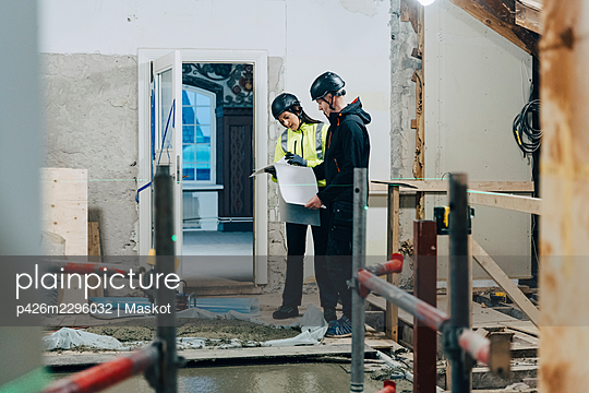 Female engineer discussing with male construction worker at site - p426m2296032 by Maskot
