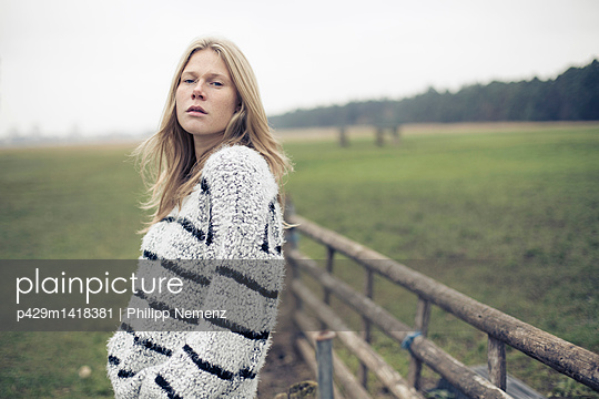 Portrait of young woman with long blond hair in rural field - p429m1418381 by Philipp Nemenz
