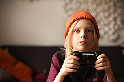 Close-up of boy playing video game at home - p1166m1142643 by Cavan Images