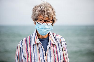 Ältere Frau mit Mundschutz - p1614m2211838 von James Godman