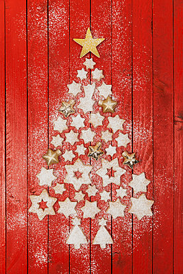 Christmas cookies and star-shaped Christmas baubles forming Christmas tree on red wooden background - p300m2012564 by Gaby Wojciech