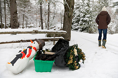 Woman disposing of festive decorations - p4297916 by Hugh Whitaker