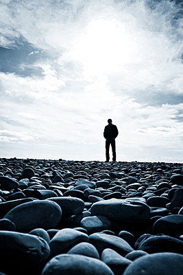 Man standing on pebble beach - p597m1488675 by Tim Robinson